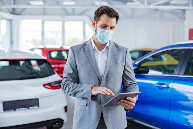 자동차 살롱에 서서 온라인 라거 확인을 위해 태블릿을 사용하는 얼굴 마스크가있는 자동차 판매자