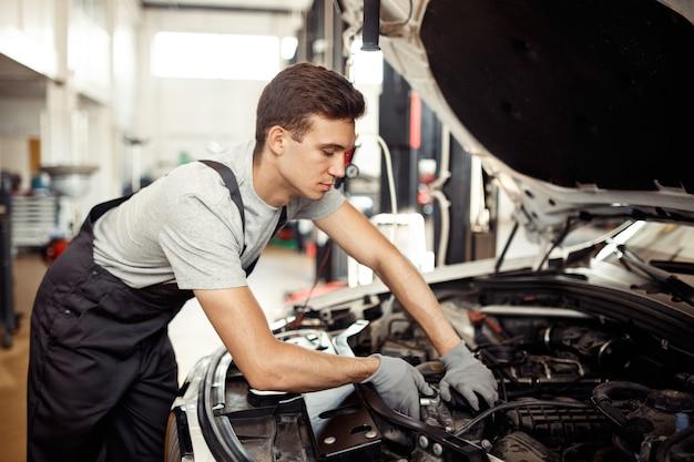 Автосервис и ремонт: автомеханик ремонтирует транспортное средство.