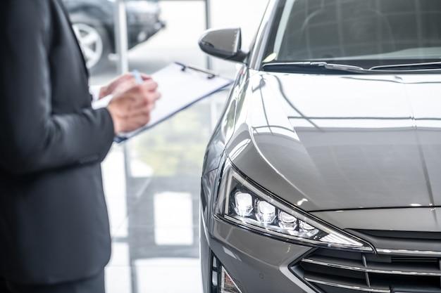 Автосервис. мужчина в деловом костюме пишет ручкой в документе, стоящем возле новой машины в автосалоне, его лица не видно