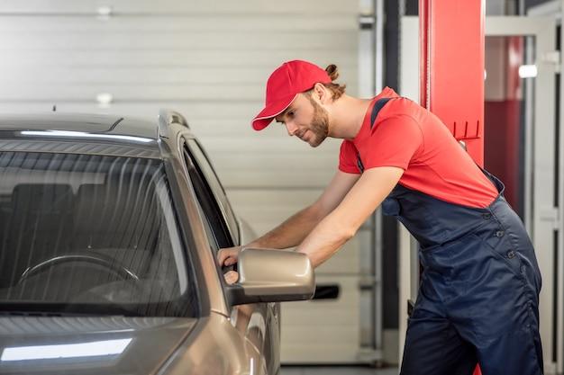 カーサービス。彼の手で触れている車の開いた窓の近くに立っている作業服の若い大人の自動車整備士のプロフィール
