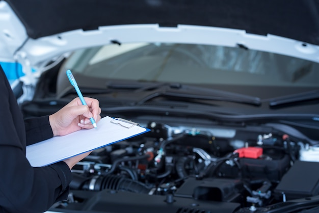 Car service, repair, maintenance concept - asian auto mechanic man or smith writing to the clipboard at workshop or warehouse, technician doing the checklist for repair machine for a new car