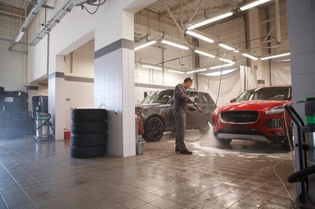 Работник автосервиса моет машины в гараже автомойки