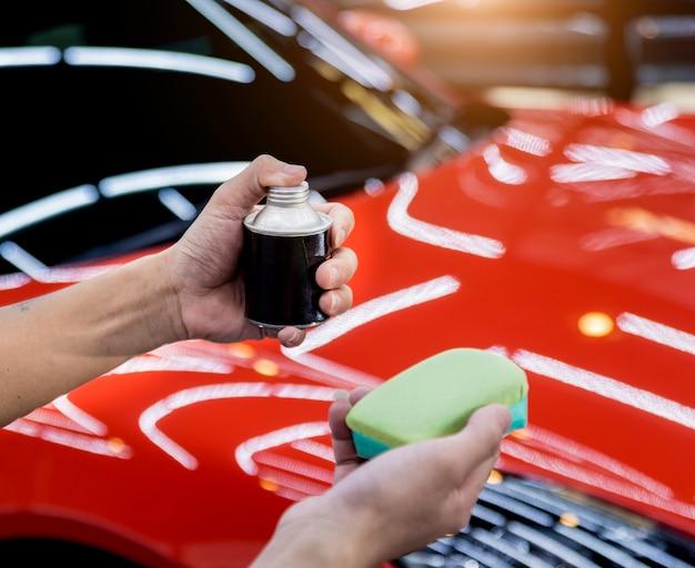 Car service worker applying nano coating on a car detail