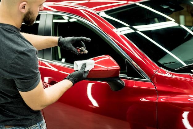 車の細部にナノコーティングを施す自動車サービス労働者。