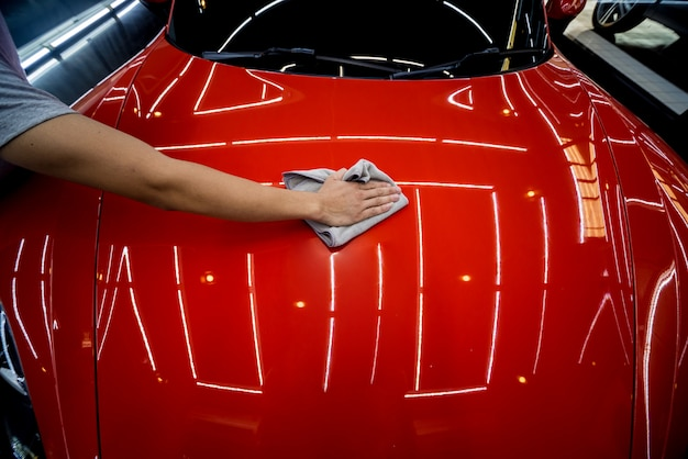 Работник автосервиса наносит нано покрытие на детали автомобиля