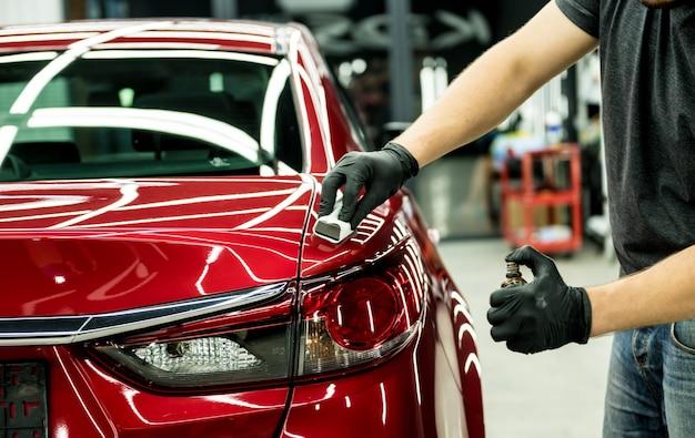 Работник автосервиса наносит нанопокрытие на деталь автомобиля.