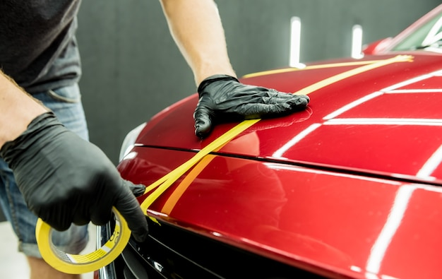 Car service worker applying protective tape on the car details before polishing.