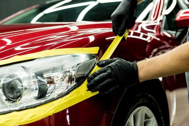 Работник автосервиса наклеивает на детали автомобиля защитную ленту перед полировкой.