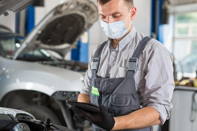 車のサービスワーカーは部屋で診断と車の修理を行います。