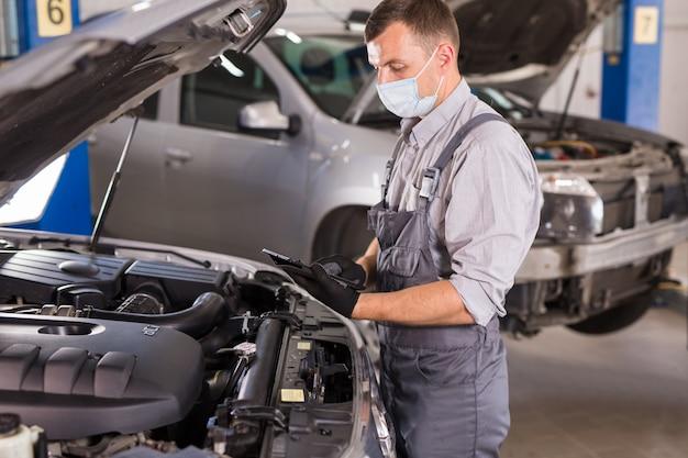 Работник автосервиса проводит диагностику и ремонт автомобилей в помещении.