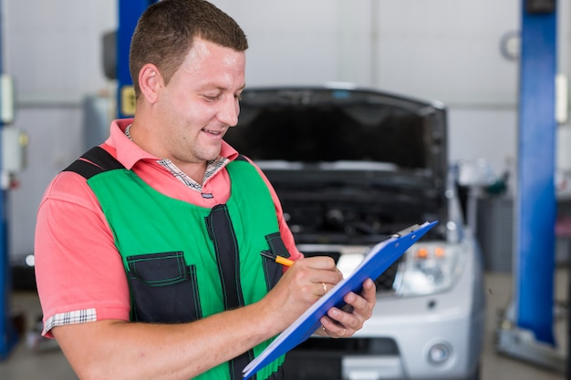 Car service worker carries out diagnostics and car repairs in the room.