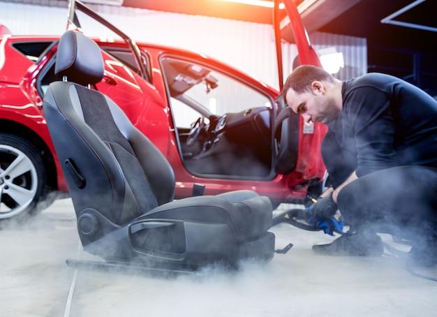 Работник автосервиса чистит автокресло пароочистителем