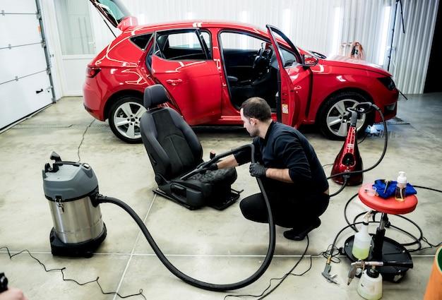 진공 청소기로 자동차 좌석 청소 자동차 서비스 노동자