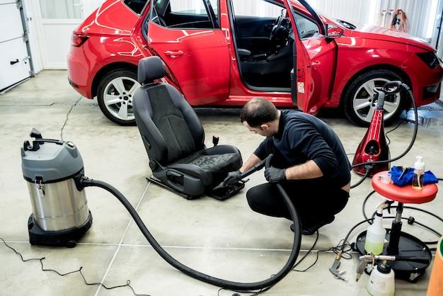 Работник автосервиса, чистящий автокресло с пылесосом