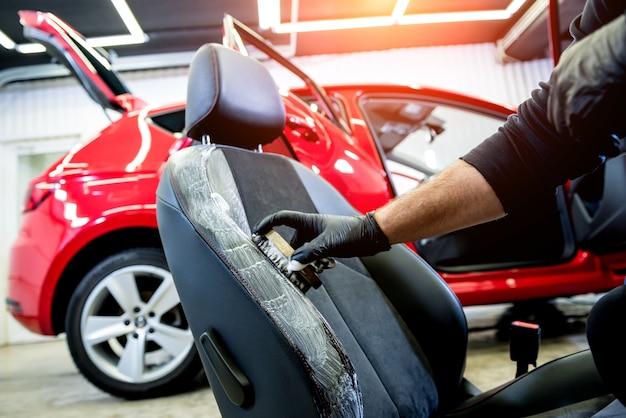 자동차 서비스 작업자가 특수 브러시로 자동차 시트를 청소합니다.