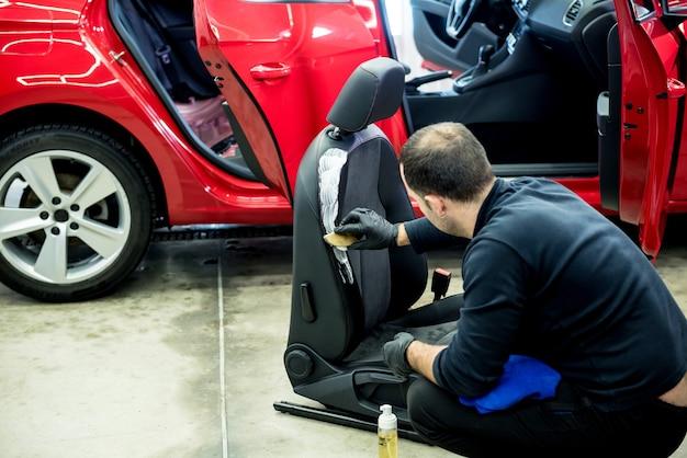 Работник автосервиса чистит автокресло специальной щеткой