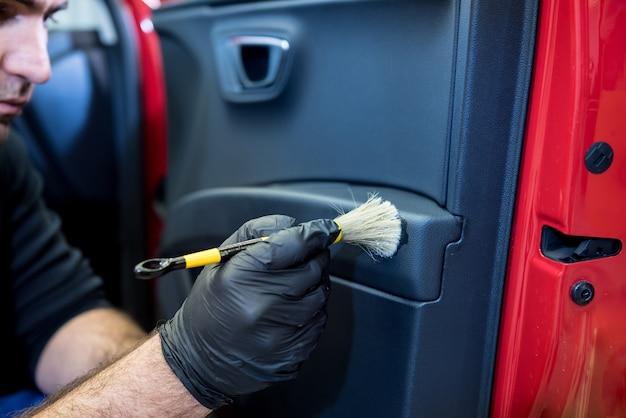자동차 서비스 작업자가 특수 브러시로 interiror를 청소합니다.