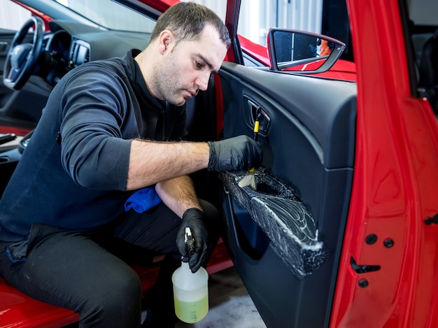 Работник автосервиса чистит салон специальной щеткой