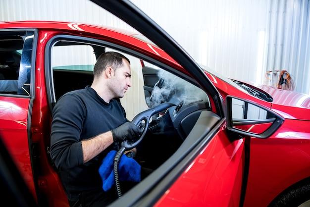 자동차 서비스 작업자가 스팀 청소기로 interiror를 청소합니다.