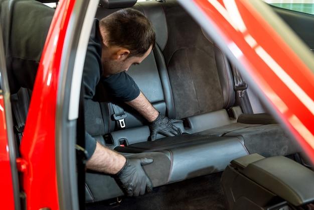 Работник автосервиса разбирает салон автомобиля