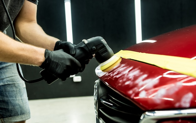Работник автосервиса полирует детали автомобиля орбитальной полировальной машинкой.