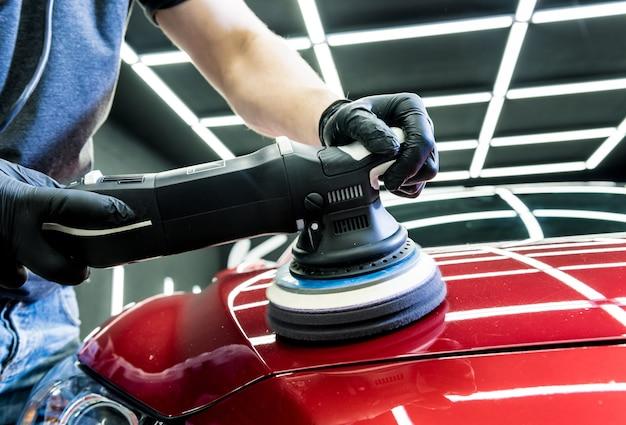 車のサービスワーカーは、軌道研磨機で車の細部を研磨します。