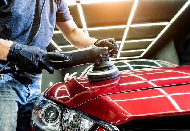 Работник автосервиса, полируя автомобиль
