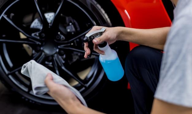 車のサービスワーカーは、マイクロファイバーの布で車のホイールを研磨します。