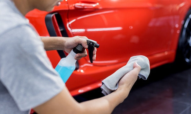 Car service worker polishing car wheels with microfiber cloth.