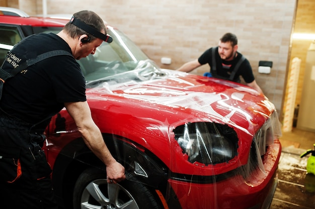 カーサービスワーカーは、詳細車両ワークショップで赤い車体に砂利防止フィルムを貼りました