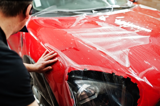 Работник автосервиса наклеил антигравийную пленку на красный кузов автомобиля в мастерской по ремонту автомобилей