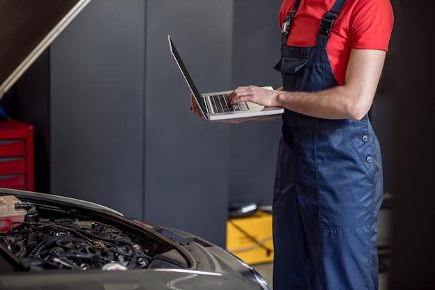 Автосервис, мастерская. сильные мужские руки, работающие на ноутбуке возле открытого капота автомобиля в автомастерской