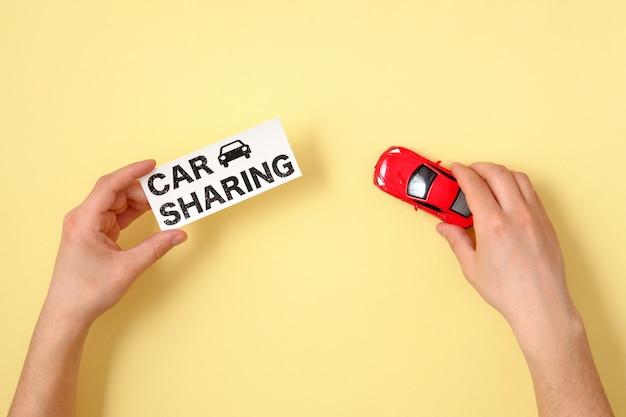 Концепция обмена автомобиля. человеческие руки, держа красный игрушечный автомобиль модели и текстовый знак «автомобиль обмена» на желтом фоне. вид сверху.