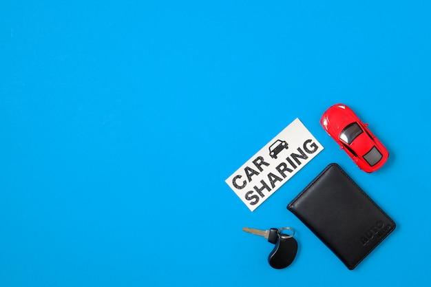 Концепция совместного использования автомобиля с игрушечным автомобилем, водительские права, ключ от машины, текстовый знак «разделение автомобиля». автомобильный обмен бизнесом, сервис обмена автомобилями. плоская планировка. вид сверху