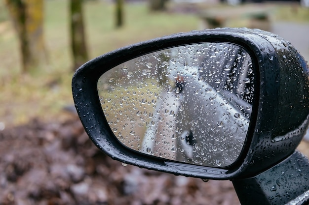 Car side rear view mirror with rain drops on blurred background rainy day on the road driving in bad weather