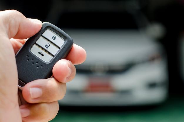 자동차 스마트 키는 전자 액세스 및 인증 시스템으로 자동차의 스마트 키를 손에 들고 있습니다.
