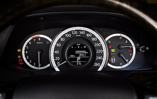 Car speedometer with kilometer per hour and tachometer,fuel meter,odometer and warning light on a car dashboard.