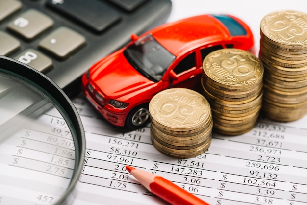Car; stack of coins; colored pencil; calculator and magnifying glass on financial report