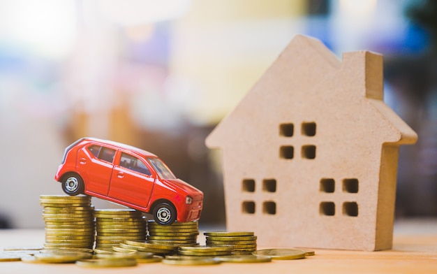 Car on stack of coins and wooden house