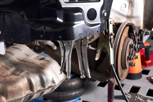 Автомобиль стоит на подъемной платформе для ремонта в автосервисе