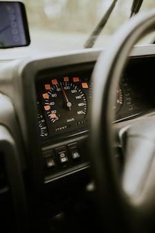 車のステアリングホイールとラベル付きスピードメーター
