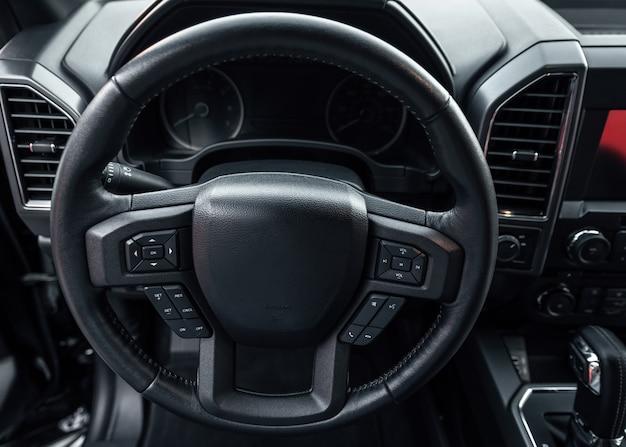 Car steering wheel. vehicle interior. interior view of car with black salon.