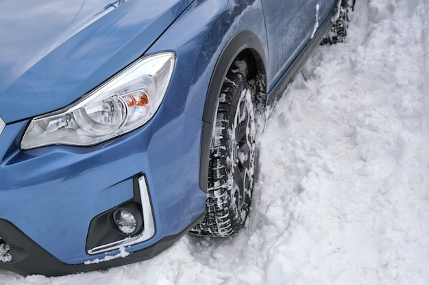 Car stuck in deep snow on cold winter day.