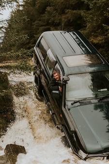 オフロードロードトリップ中に車が渓流に引っかかった