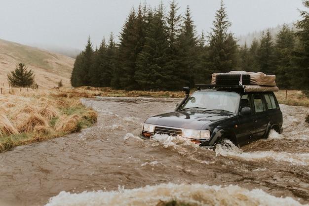 車が救助を待っている小川で立ち往生