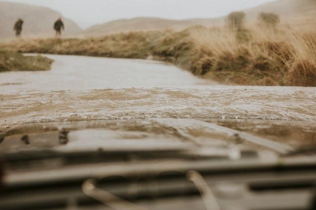 車が運転手と救助に来る人々からの水の眺めで立ち往生