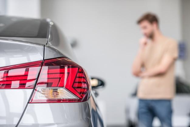 車、テールライト。自動車販売店にある新しい乗用車と遠くに立っている物思いにふける男性のリアライトのビュー