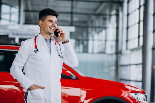 Car technician with stethoscope in a car showroom talking on the phone
