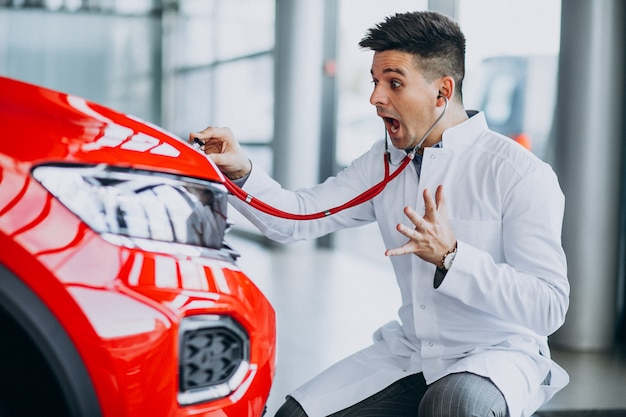 Car technician with stethoscope in a car showroom