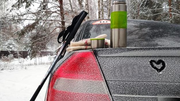 Машина, термос, лыжные палки в зимнем лесу